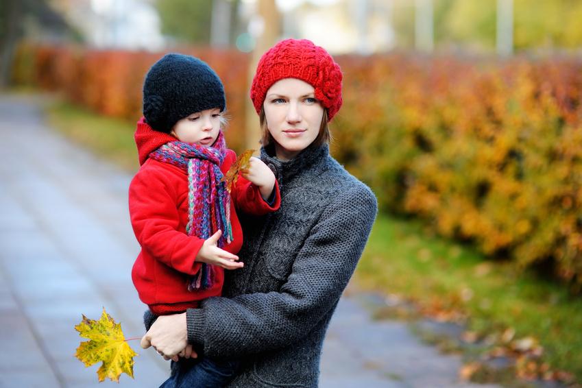 Young mother and her toddler girl in autumn